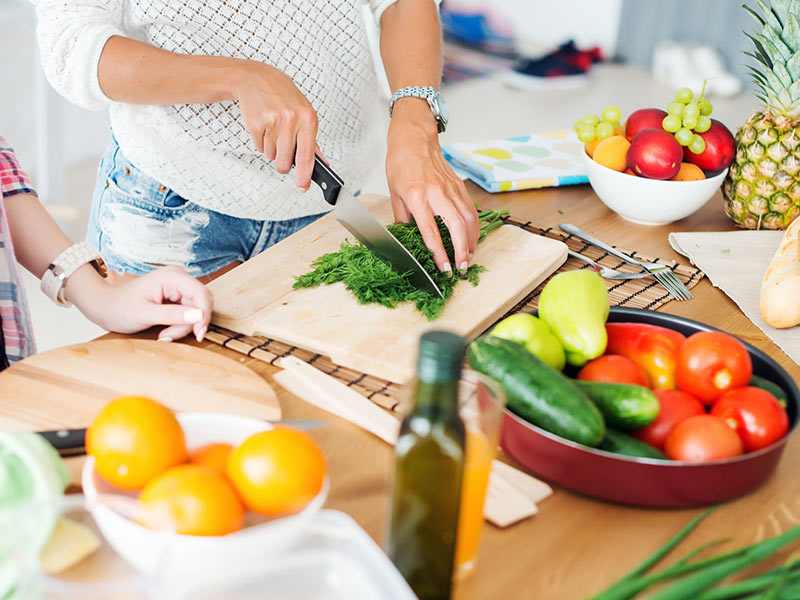 Woman cutting healthy fruits and vegetables